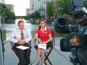 KCRG-TV 9's Bruce Aune and Beth Malicki broadcast from the water's edge after evacuating the downtown studio